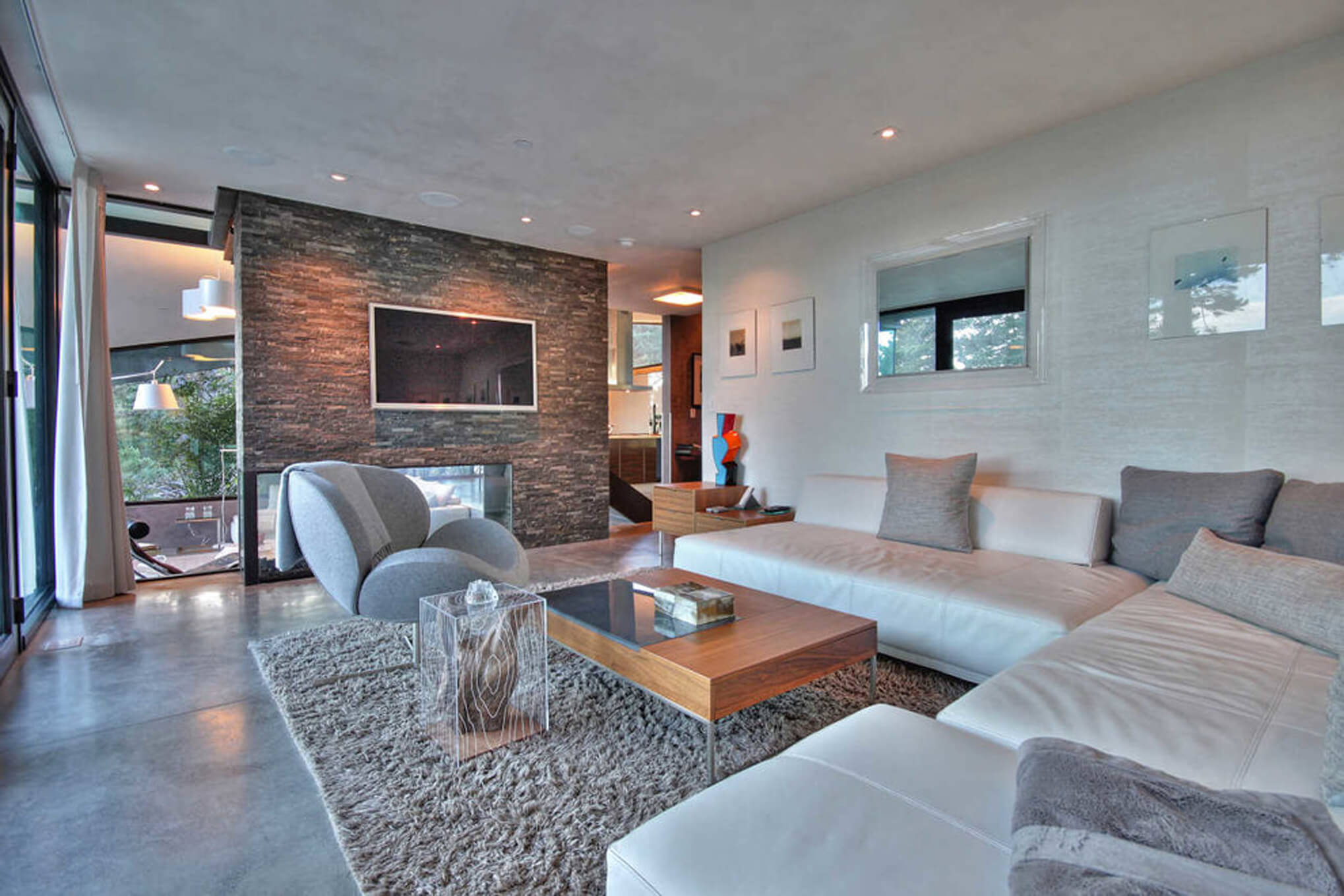 Informal living room with natural stone textures and sweeping views of the coast by Interior Designer, RM Interiors.