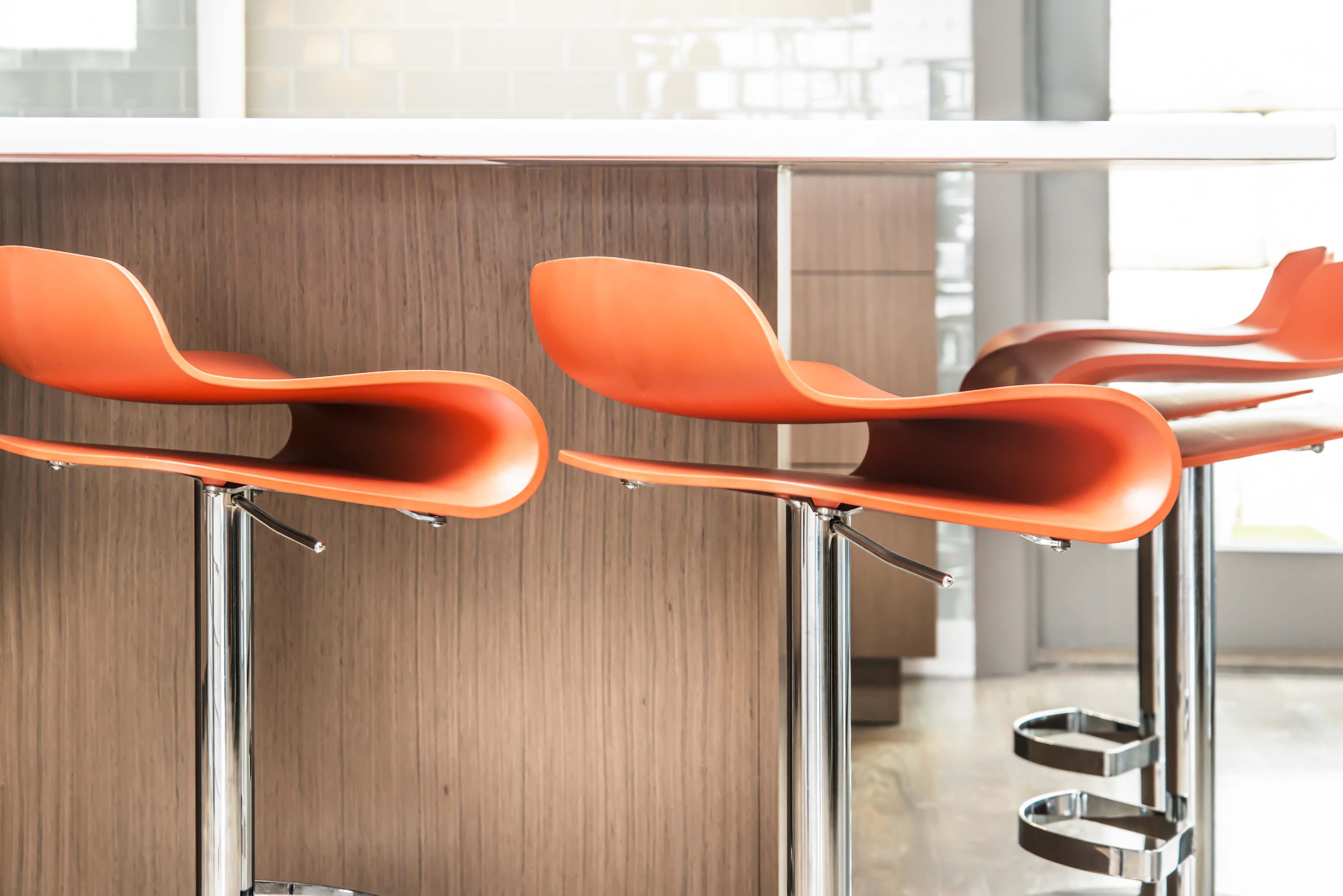Detail shot of modern orange stools in a contemporary kitchen. Designed by Cincinnati Interior Designer, RM Interiors.