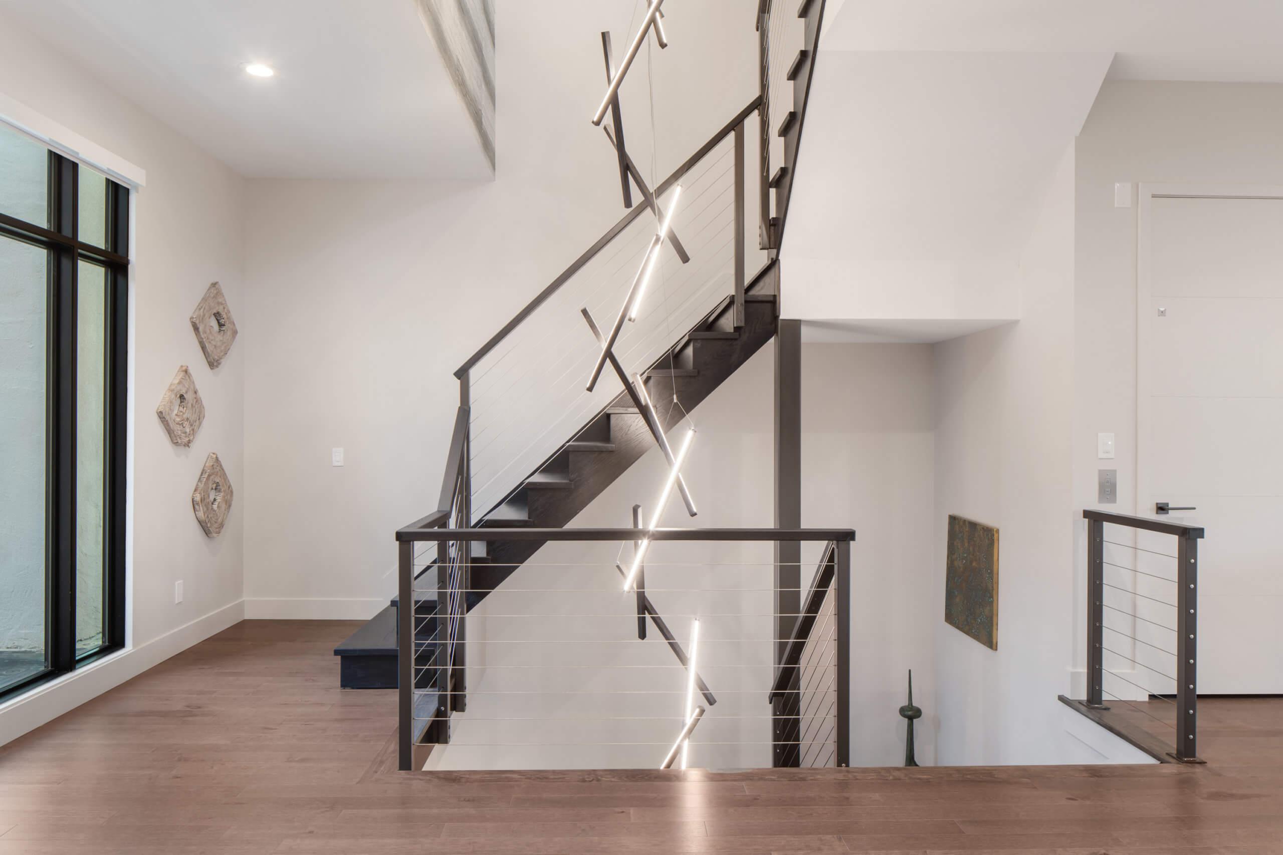 Open stairway features a custom 3 story tall chandelier. Lighting design and interiors designed by Cincinnati's premiere contemporary interior designer, Renan Menninger.