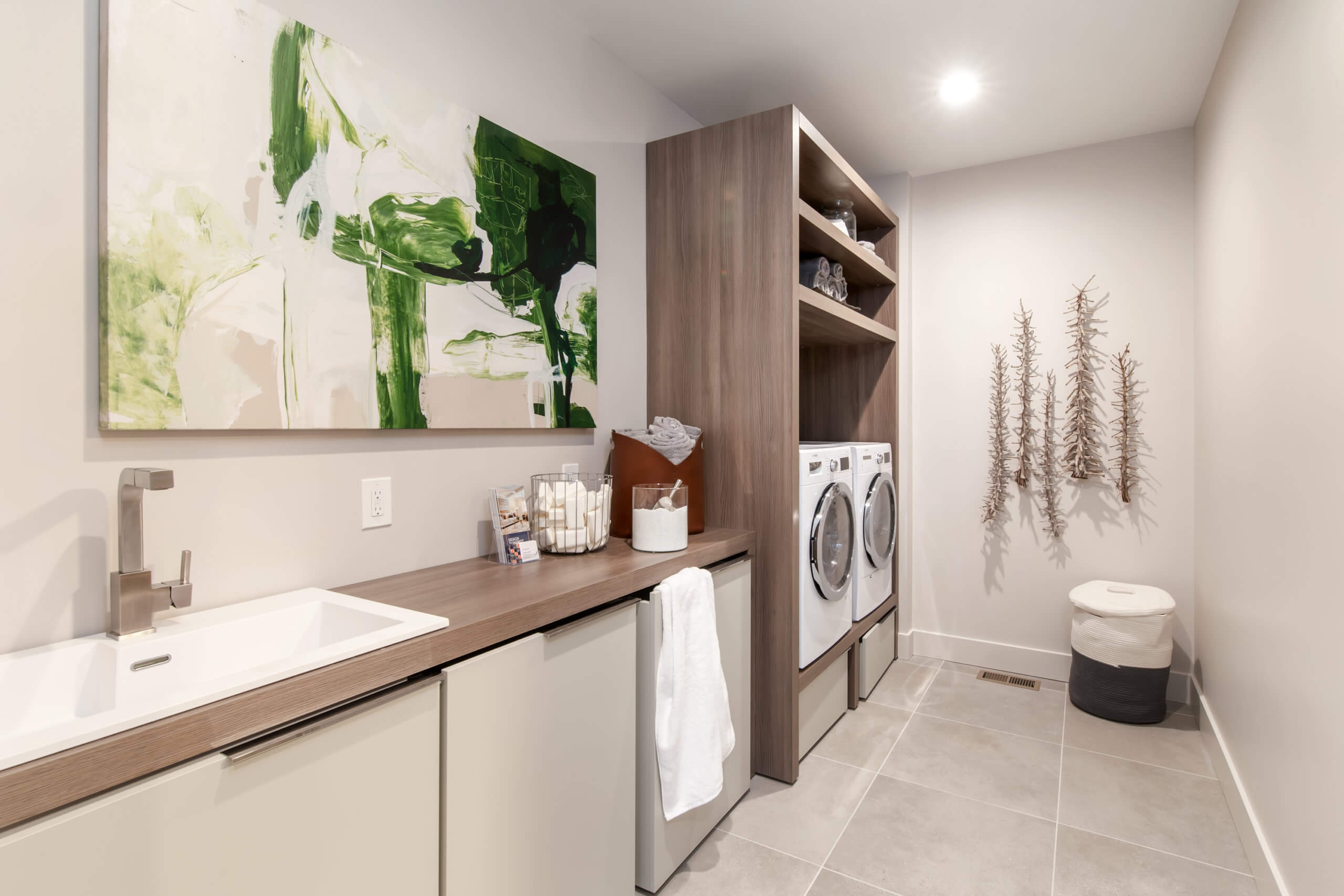 Modern and functional laundry room with custom cabinetry and laundry sink in a custom home located in Cincinnati. Room designed by interior designer, RM Interiors.