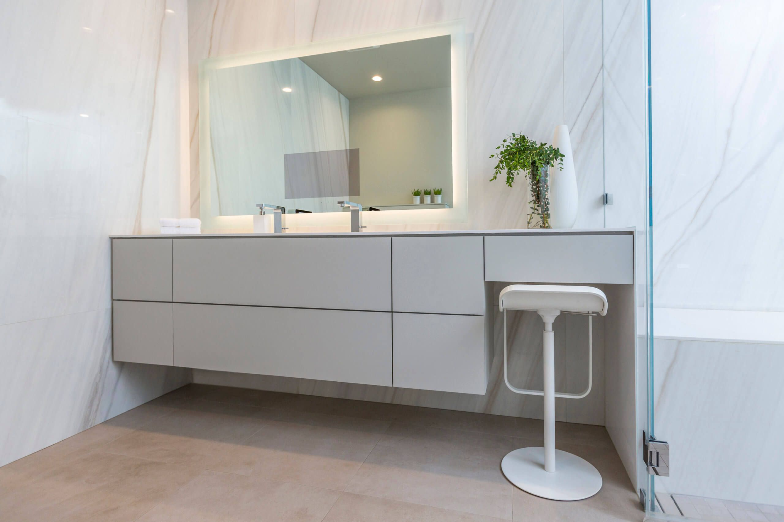 White natural stone modern bathroom with custom cabinetry and touch screen mirror. Bathroom Designed by premiere Cincinnati interior Designer, RM Interiors.
