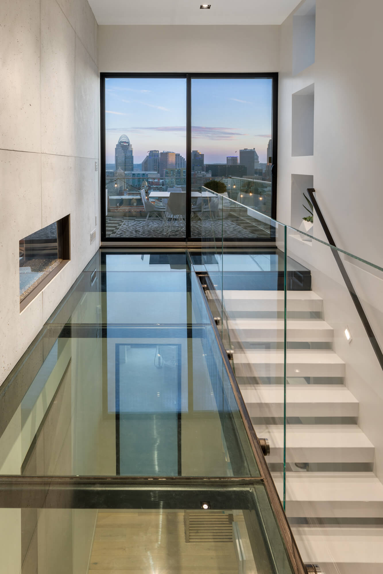 Custom Starway and glass floor hallway with Cincinnati Skyline views by Premiere Interior Designer, RM Interiors