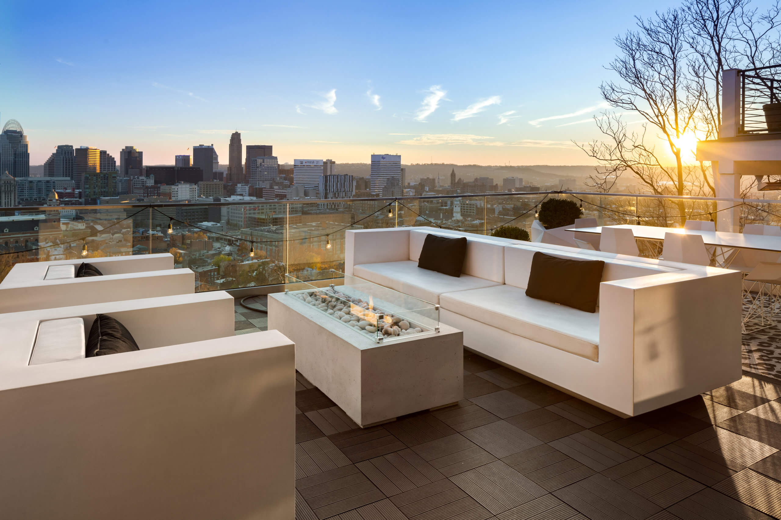 Sunset view of the Cincinnati Skyline from a Modern Rooftop Designed by Premiere Cincinnati Interior Designer, RM Interiors.