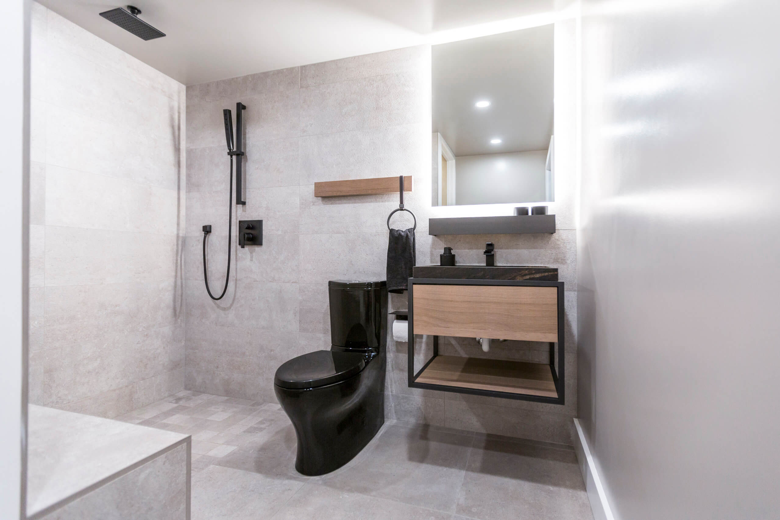 Contemporary tile bathroom with backlit mirror, black toilet and natural wood accents on the custom vanity. Designed by interior designer, RM Interiors.