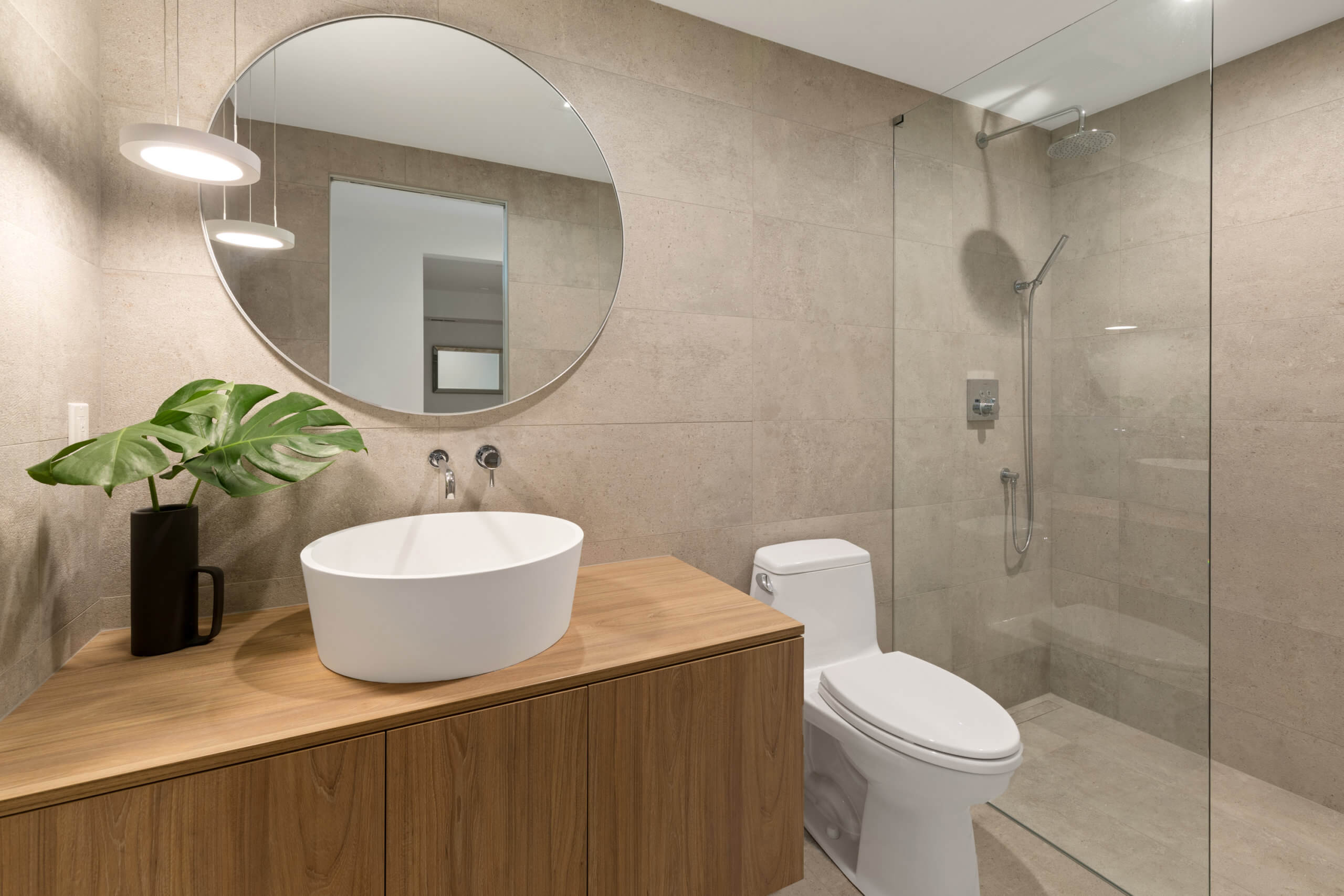 Clean and modern bathroom with custom cabinetry and glass shower, designed by Cincinnati Interior Designer, RM Interiors